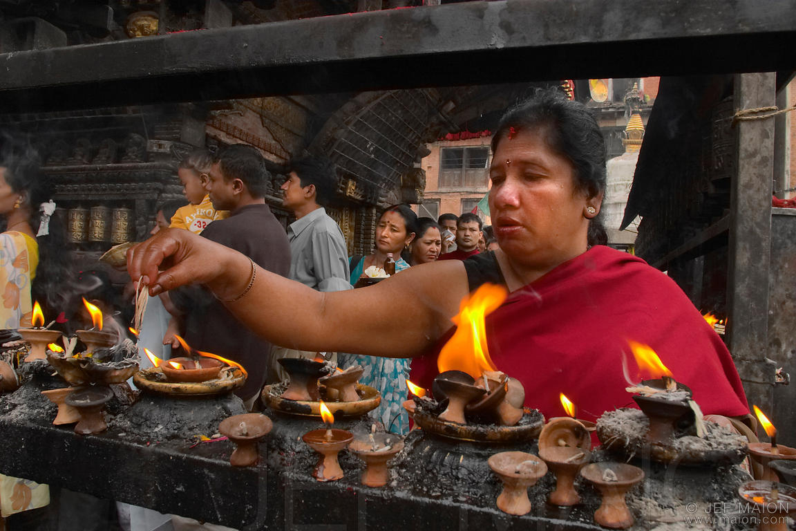 Woman lighting a candel at Swayambhu Nath temple