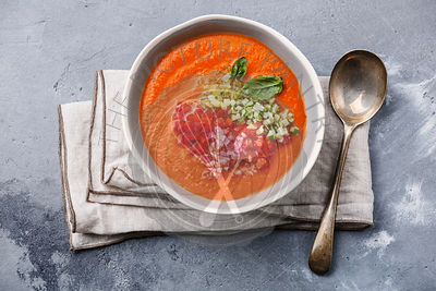Gazpacho soup served with basil and chopped vegetables on grey concrete background