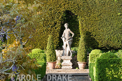 Italian marble statue of youth on the Great Terrace, set against a yew hedge and framed with box cones. Iford Manor, Bradford-on-Avon, Wiltshire