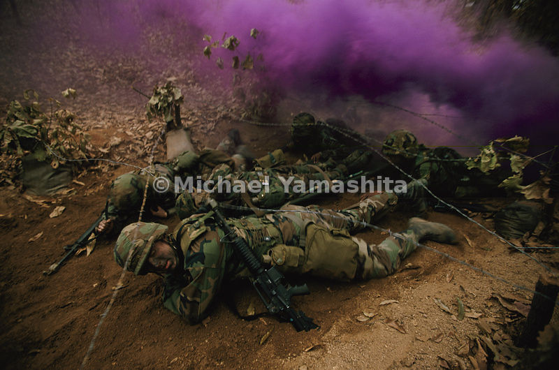 "Smoke bombs and the sounds of artillery and sniper fire simulate battle as medics practice evacuating a soldier under barbed wire. Says a U.S officer: ""We train on the ground we'll fight on. And it doesn't take two days to get ready."" If called apon, he says, ""we'll fight tonight."""