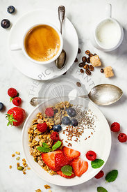 Healthy breakfast with coffee, yogurt, granola and berries