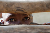 Shy Kenyan child looking through rails. Kenya