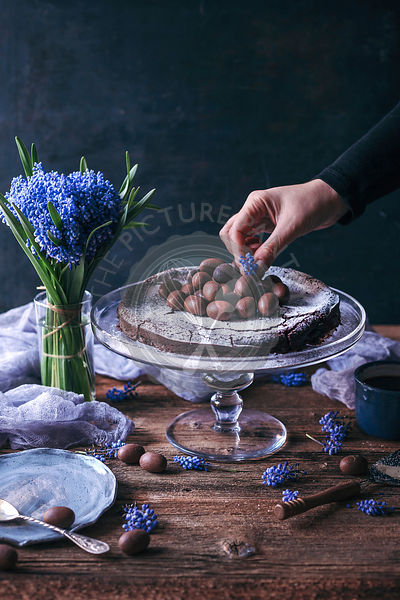 Woman decorating Swedish chocolate cake on a cake stand with chocolate eggs and flowers