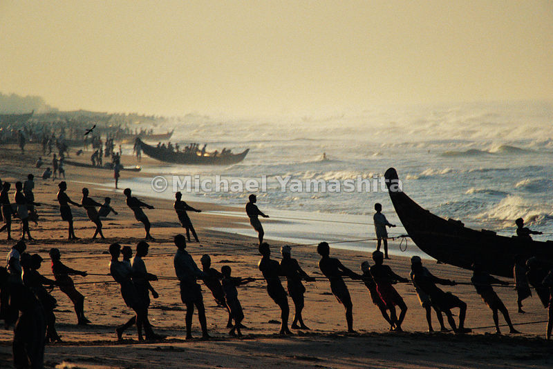 While the sun dissolves the mist, fisherman of Kovalom pull their nets into the shallow waters. Kerala, India.