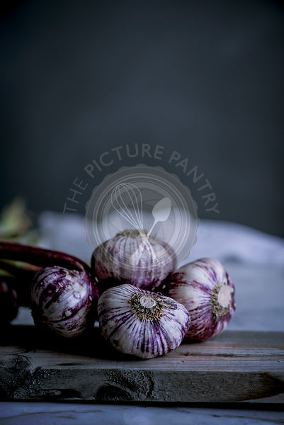 Purple and white garlic bulbs in a rustic kitchen