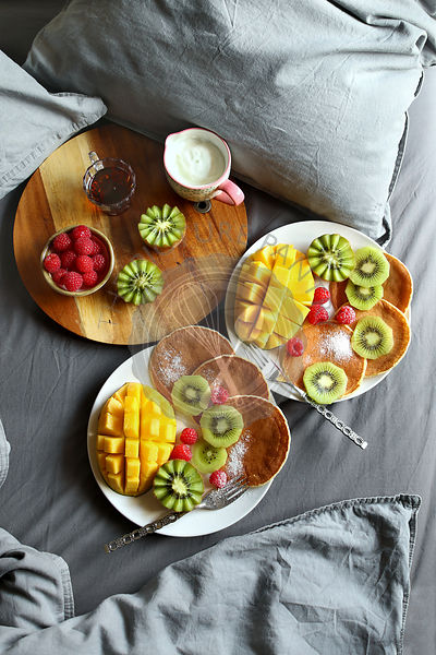 Breakfast served in bed with pancakes,fresh fruit,yogurt and maple syrup