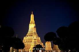 An evening view of the illuminated Wat Arun in Bangkok, Thailand.