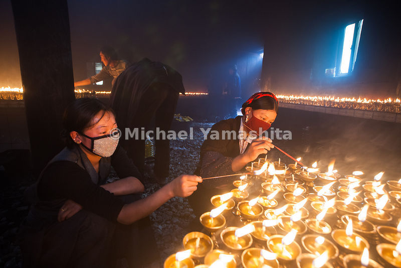 The faithful light yak butter lamps in honor of a living Buddha during an 18-day festival of prayers in Bame.
