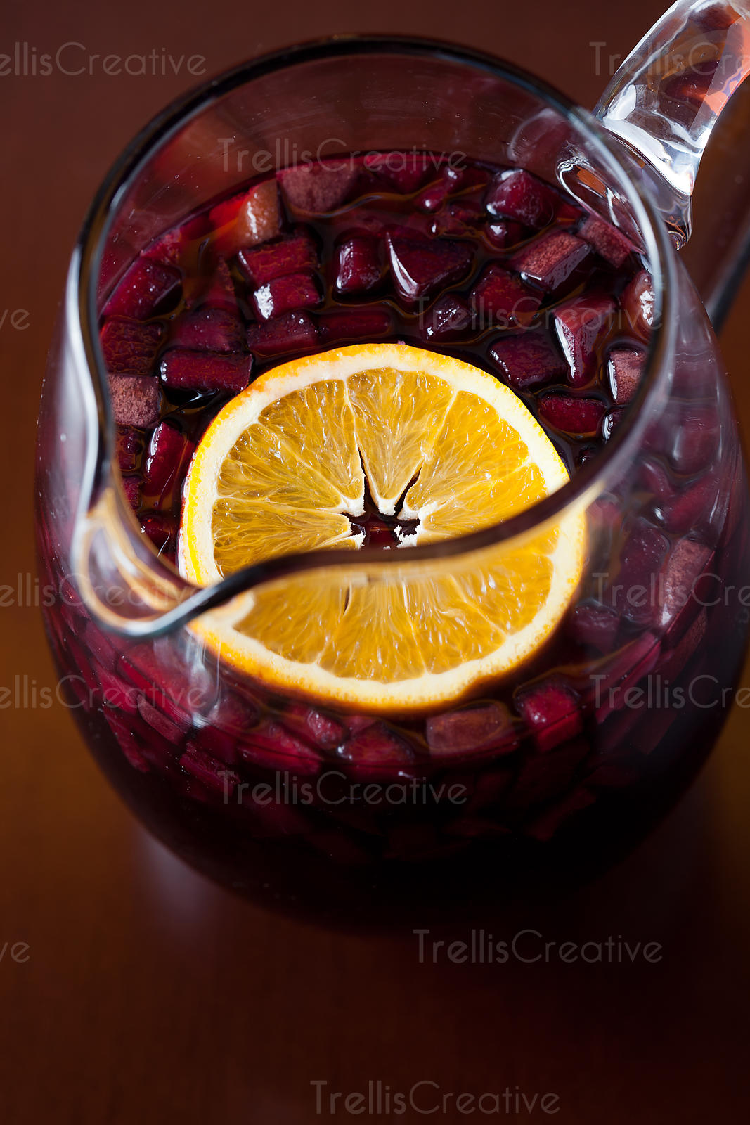 An fresh orange slice floating with mixed fruit in a pitcher of sangria