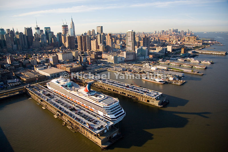The growing interest in cruising has revived the Passenger Ship Terminals on the Hudson River. A Carnival cruise ship anchors near the Intrepid Sea, Air, Space Museum.  Manhattan, New York City.