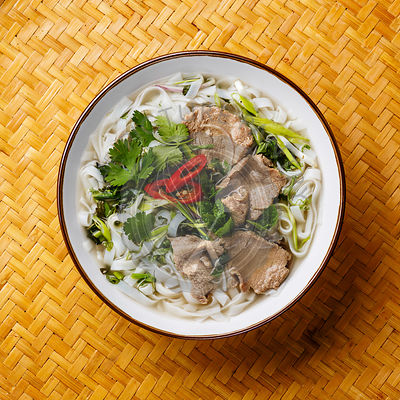 Pho Bo vietnamese Soup with beef on bamboo tray background close-up