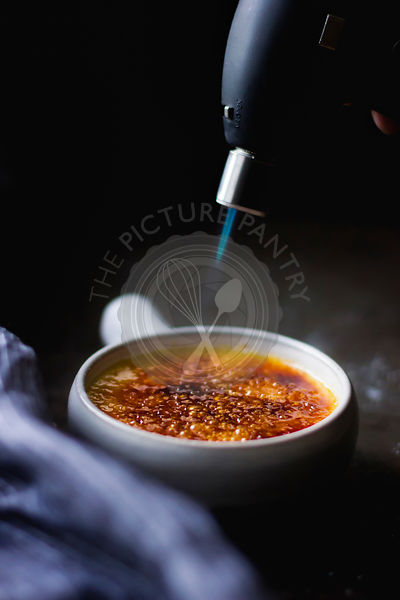 Melting sugar on a creme brulee dessert with a blow torch