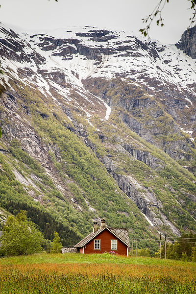 Traditional Red Timber House with a Snow-Capped Mountain Behind
