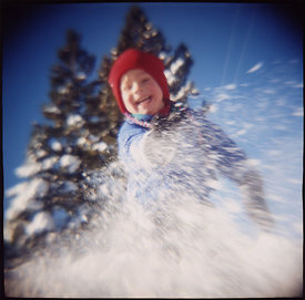 boy splashes snow at camera
