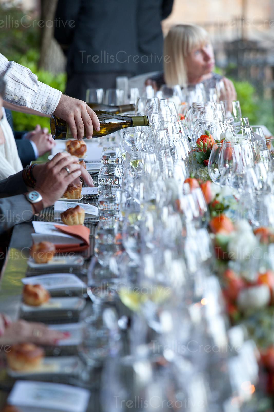 Waiter pouring wine into wineglass at wedding reception