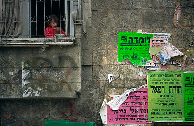 A child peers out of a barred window in the Orthadox Jewish ghetto of Meir Sharim, Jerusalem