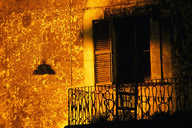 Warm sunlight casting shadows on a wrought iron balcony and window shutters
