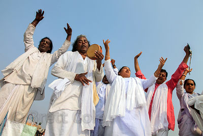 Pilgrims in white pray on the beach at the Gangasagar Mela (festival), a pilgrimage to Sagar Island in India, where the Ganges River meets the sea.