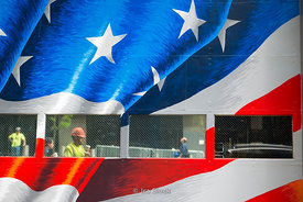 American flag painted on wall and reflection of people walking on the street around National September 11 Memorial & Museum in New York.