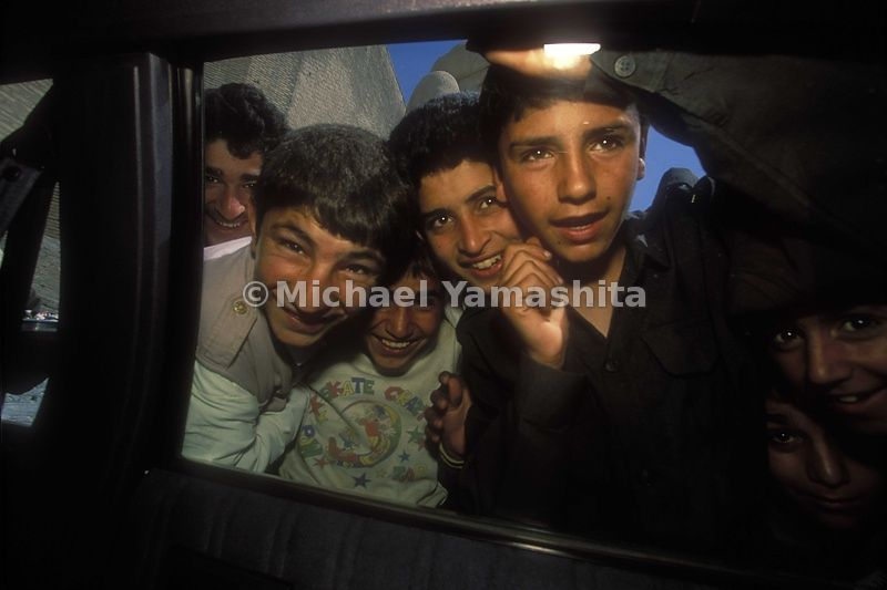Iraqi boys peer through a car window.