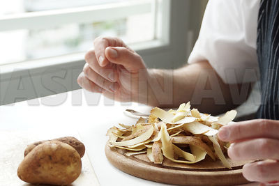 Peeling potatoes at home in the kitchen