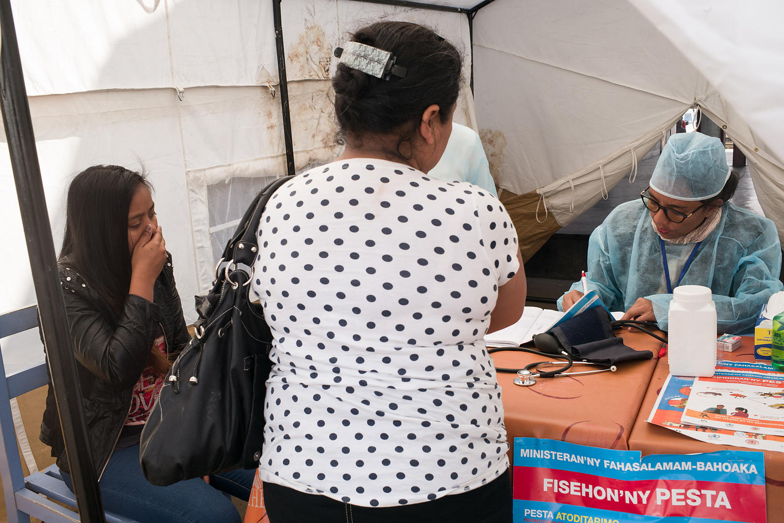 "A young woman (L) gestures as she is examined by a doctors at a healthcare checkpoint at the ""taxi-brousse"" station of Ampasapito district in Antananarivo on October 5, 2017, with the mission of informing passengers leaving Antananarivo, and to potentially detect cases suspected of plague."
