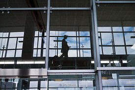 Reflection of passengers walking at the terminal in Oslo Airport, Norway.