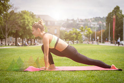 Young woman practicing yoga in a park in the city