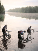 Adventure racers crossing lake with bikes
