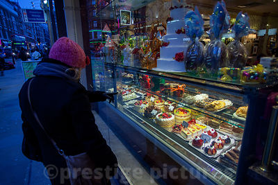 Woman looks at tempting display of Cream Cakes in Shop Window