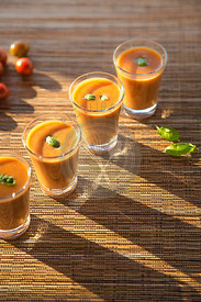 outdoors shot of tomato gazpacho or soup in glasses with basil on woven bamboo mat