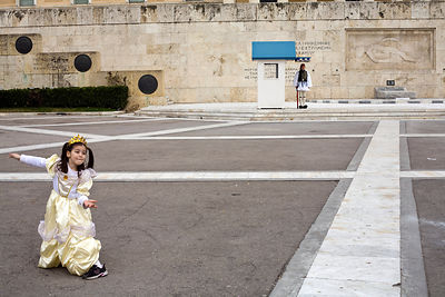 Greece - Athens - A child in costume plays in front of a sentry during the Changing of the Guard
