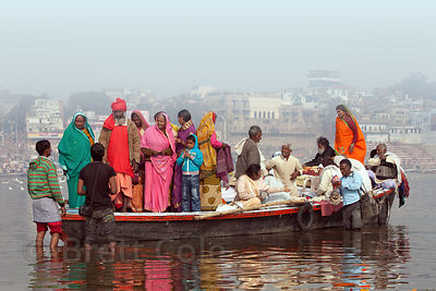 Men hawk jewelry and souvenirs to Hindu pilgrims riding in boats on the Ganges River, Varanasi, India.