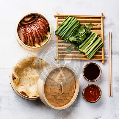 Sliced Peking Duck in bamboo steamer served with fresh cucumber, green onions, cilantro and roasted wheaten chinese pancakes with sauce Hoysin on white background