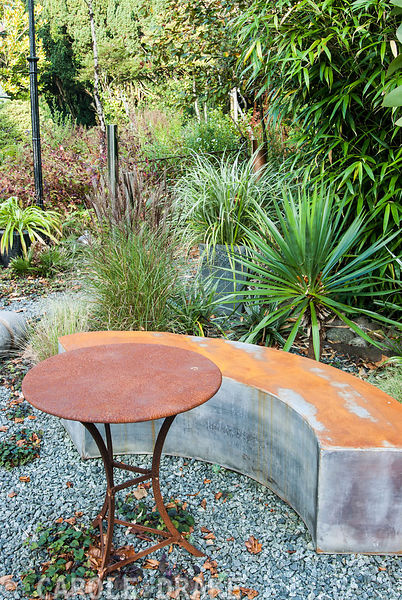 Metallic bench and table surrounded by strong foliage plants including pencil cypress, Cupressus sempervirens, acer and tree fern. The Cors, Laugharne, Camarthenshire, Wales, UK