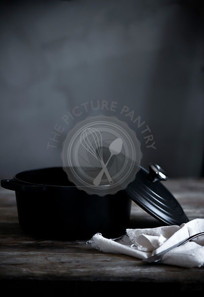 A black casserole dish on a wooden table