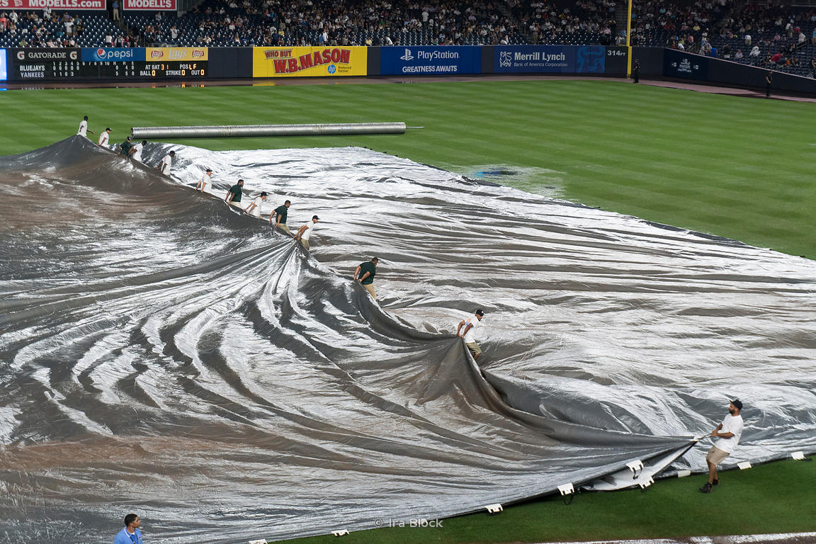 Groundkeepers cover the in-field with a tarp during a rain-delay at  Yankee Stadium