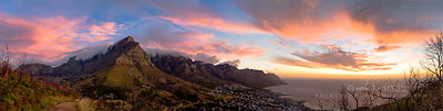 Panoramic view of Table Mountain and the Twelve Apostles above Camps Bay, with pink clouds lit by the setting sun, viewed from Lion's Head