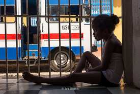 A young girl sitting on the window sill and looking at the street in Trinidad, Cuba