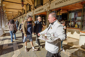 VENICE, ITALY - OCTOBER 23, 2017: A waiter serving coffee on a sunny morning in Piazza San Marco in Vencie Italy.
