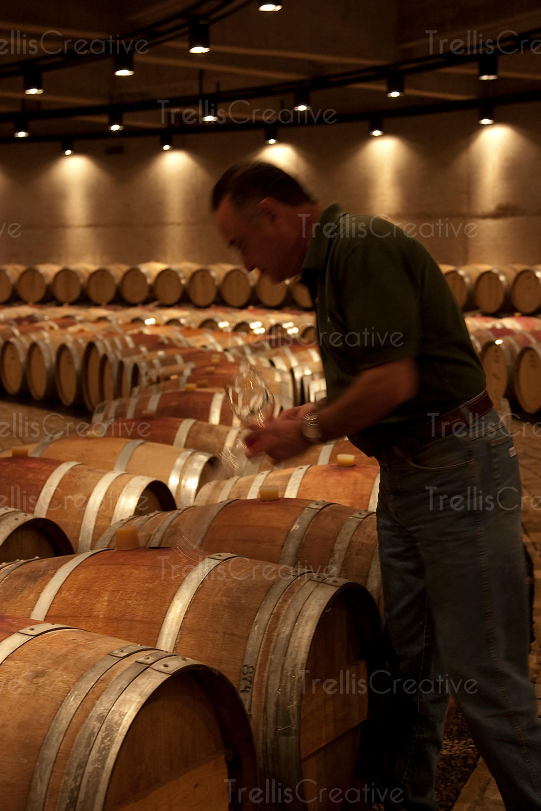 A winemaker samples wine from the barrel in a wine cave
