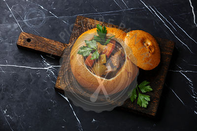 Beef meat soup Goulash stewed with potato, carrot and spices in Bread on black marble background