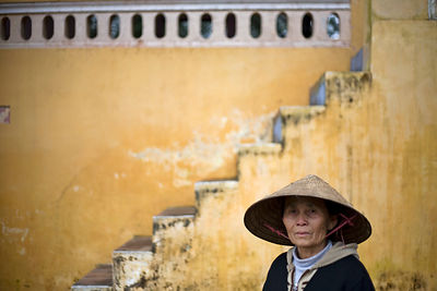 Vietnam - Hue. An old woman in traditional Vietnamese dress in the Gardens at the Thienmu Pagoda