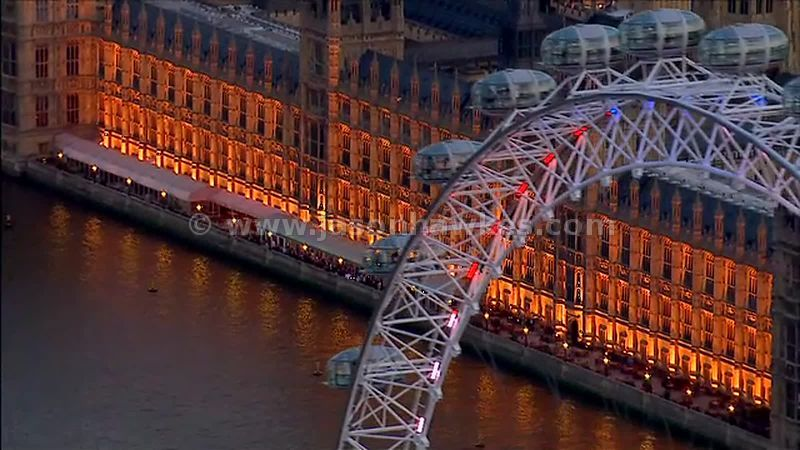 Aerial footage of the London Eye and Houses of Parliament at night, London, England UK