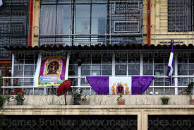 Señor de Milagros banners hanging on balcony of apartment block during festival, Lima, Peru