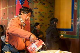 A man pouring liquid yak butter into candles  at Dreprung Monastery in Lhasa, Tibet.