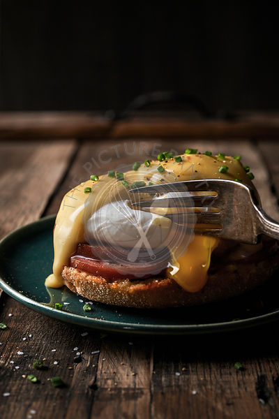 Close-up image of eggs benedict on a rustic wood surface.