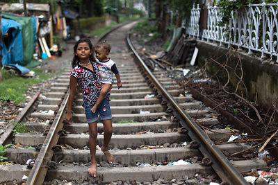 Girl and her baby brother walk along railway track, BBD Bagh, Kolkata, India