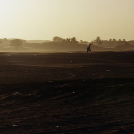A man walks through the dunes that surround Chinguetti in a sandstorm. Mauritania