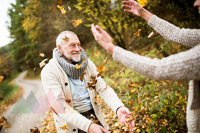 Happy senior man and his wife playing with autumn leaves